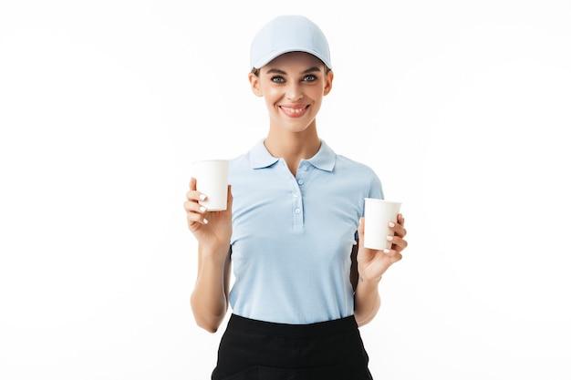 Menina alegre em uma camiseta polo azul e boné segurando copos descartáveis enquanto feliz