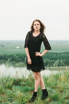 Menina alegre em vestido preto landim está dançando no prado na colina acima do rio