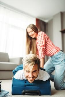 Menina alegre embalou o marido em uma mala