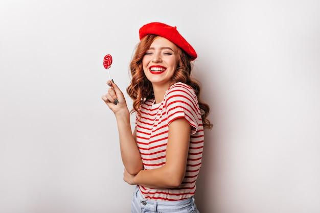 Menina alegre encaracolada com pirulito expressando felicidade. jovem francesa bonita com doces rindo na parede branca.