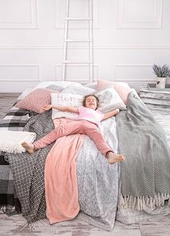 Menina alegre encontra-se na cama com lindos cobertores e travesseiros.