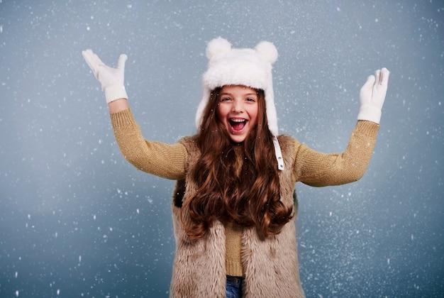 Menina alegre entre neve caindo