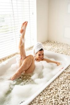 Menina alegre está brincando com espuma enquanto toma banho no spa. ela deita no banheiro e ri