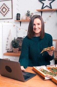 Menina alegre está sentada na cozinha, em seu laptop perto de uma pizza encomendada.