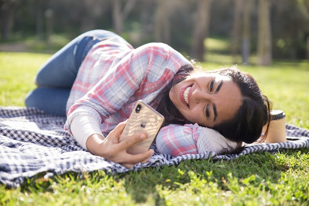Menina alegre estudante relaxado deitado no xadrez no parque
