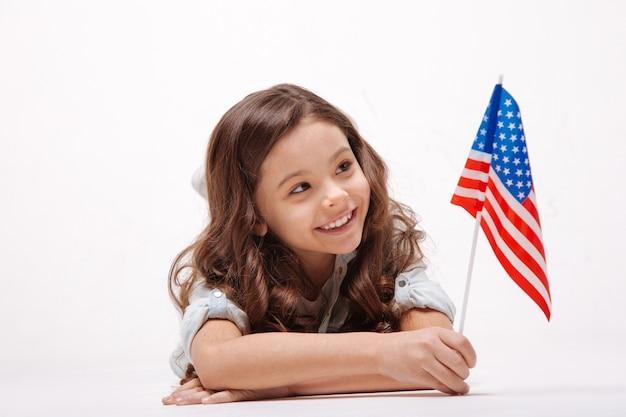 Menina alegre feliz e divertida segurando a bandeira americana enquanto expressa alegria e deitada contra uma parede branca