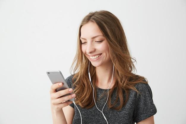Menina alegre feliz sorrindo olhando para a tela do telefone ouvindo streaming de música.