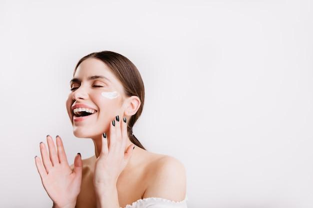 Menina alegre gosta de aplicar creme hidratante para limpar o rosto. morena sem maquiagem ri na parede branca.