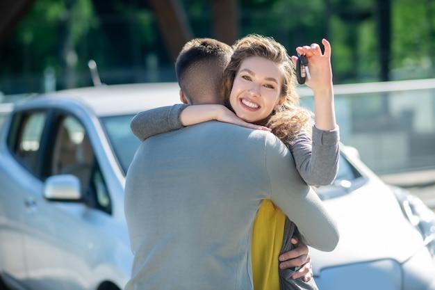 Menina alegre grata com uma chave, abraçando um homem