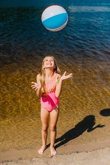 Menina alegre jogando bola de praia em pé contra o mar