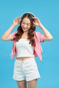 Menina alegre jovem asiática posando isolado no fundo da parede azul. ouça música com fones de ouvido, dançando