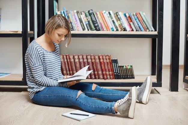 Menina alegre jovem estudante de cabelos claros, com cabelos curtos em camisa listrada e calça jeans, sentada no chão na biblioteca, lendo o livro, gastando tempo produtivo após o estudo, se preparando para os exames.