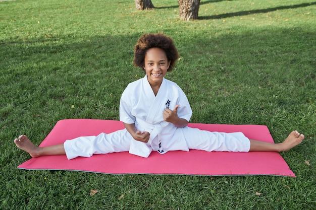 Menina alegre, karateca, sentada na esteira de ioga e levantando os polegares