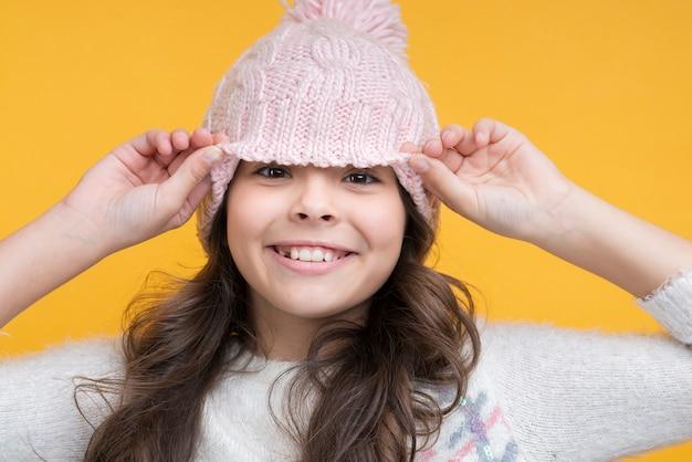 Menina alegre, levantando o chapéu do rosto