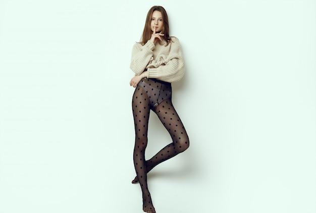 Menina alegre moda hipster de camisola aconchegante e meia-calça preta