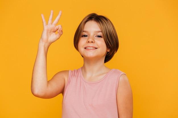 Menina alegre, mostrando o gesto ok isolado