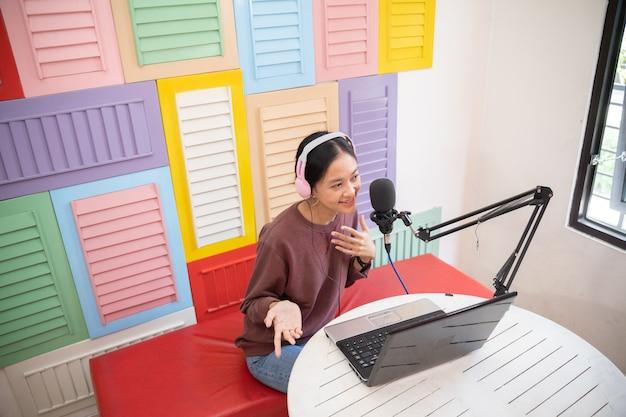 Menina alegre na frente do microfone durante o podcast
