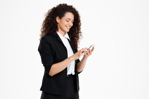 Menina alegre negócios encaracolados, olhando para o celular
