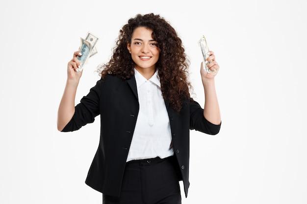 Menina alegre negócios encaracolados segurando dinheiro