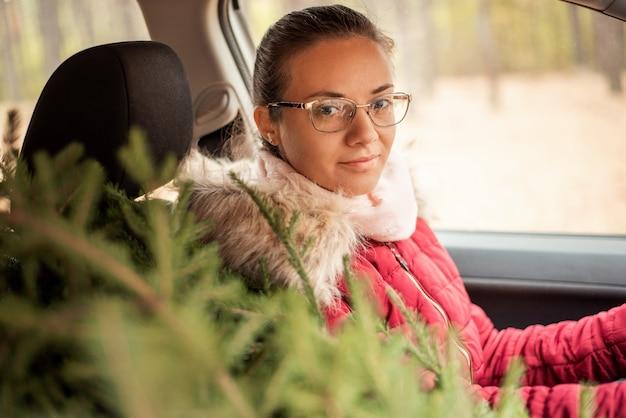 Menina alegre no carro com uma árvore de natal