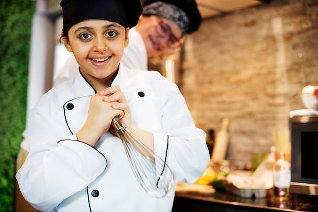 Menina alegre nova no uniforme do cozinheiro chefe