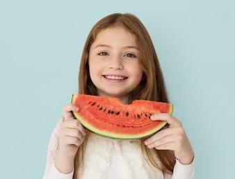 Menina alegre nova que guarda uma fatia de melancia