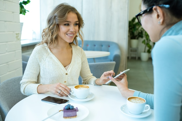 Menina alegre olhando para a amiga enquanto percorre as novas fotos no smartphone e as discute tomando uma xícara de café no café