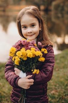 Menina alegre olhando para a câmera enquanto posa em frente a um lago com um ramo de flores
