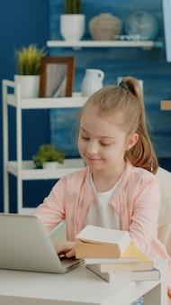 Menina alegre olhando para a tela do laptop para aulas remotas online