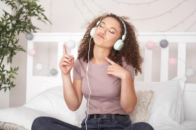 Menina alegre ouvindo música e dançando na cama