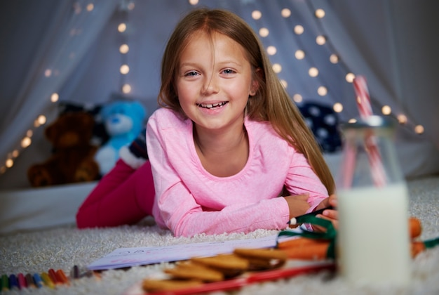 Menina alegre posando enquanto desenha