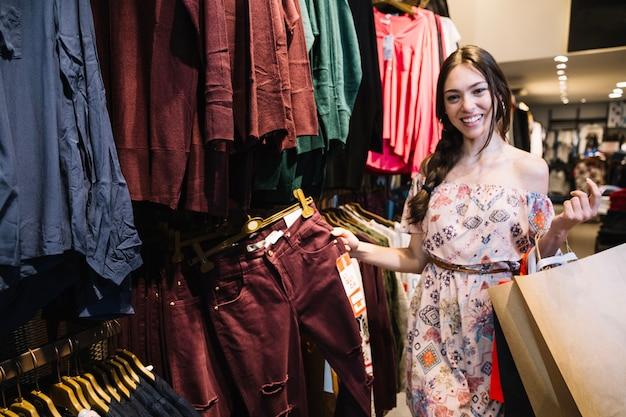 Menina alegre posando na loja de roupas