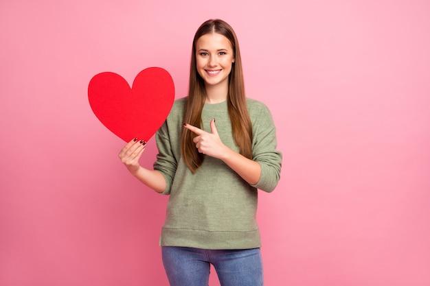 Menina alegre positiva apontar dedo indicador grande coração de cartão de papel vermelho