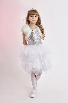 Menina alegre positiva no lindo vestido branco. jovem se divertindo e posando em fundo cinza