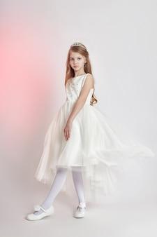 Menina alegre positiva no lindo vestido cor branca. jovem se divertindo e posando em fundo cinza. emoções de crianças brilhantes