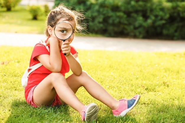 Menina alegre positiva olhando através de uma lupa ao ar livre