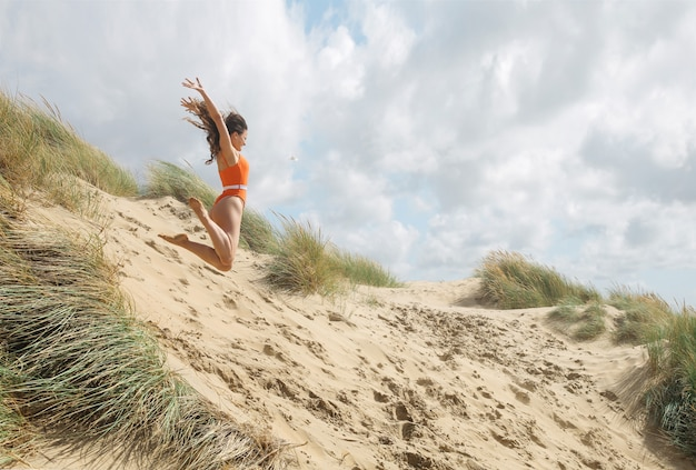 Menina alegre pulando dunas de areia