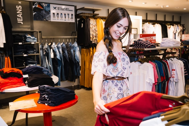 Menina alegre que explora roupas na loja