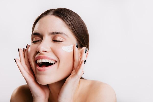 Menina alegre ri e aplica creme nutritivo no rosto. retrato de senhora sem maquiagem na parede isolada.