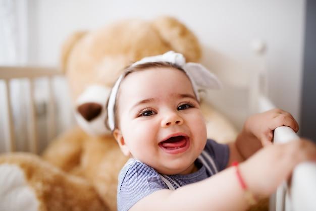 Menina alegre rindo e brincando com seu ursinho de pelúcia.