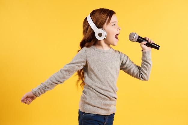 Menina alegre ruiva em fones de ouvido está cantando karaoke