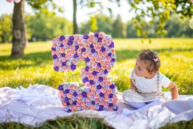 Menina alegre se divertindo no aniversário da criança em um cobertor com enfeites de papel no parque