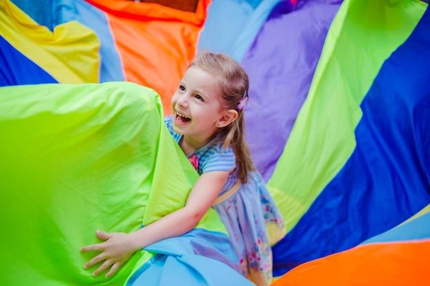 Menina alegre se divertindo, segurando um pano multicolorido e rindo