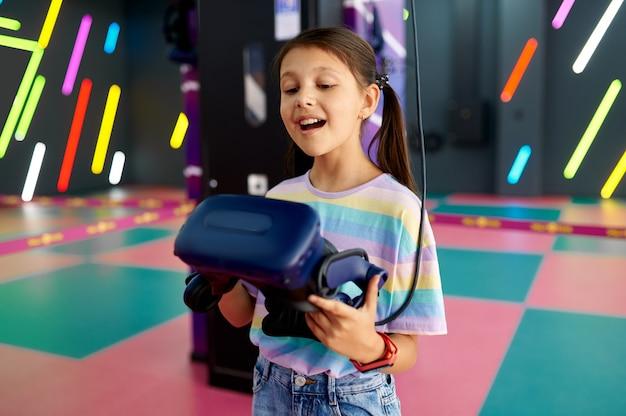 Menina alegre segurando óculos de realidade virtual