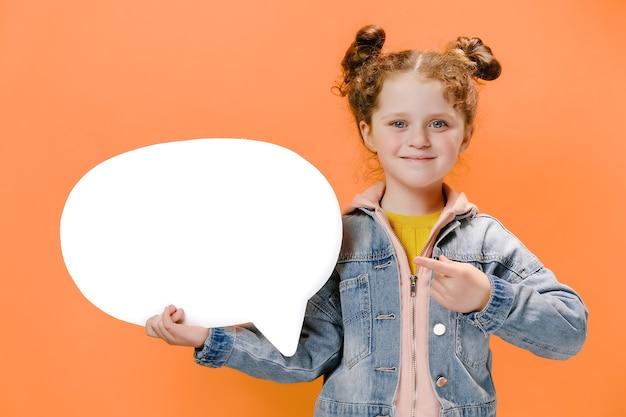 Menina alegre segurando um balão de fala e apontando para ele em fundo laranja