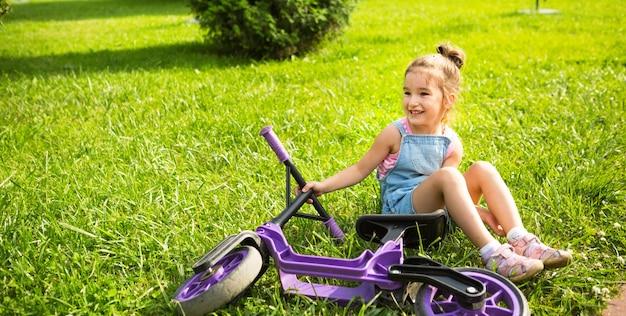 Menina alegre sentada descansando na grama em um parque perto da bicicleta de corrida roxa no verão. entretenimento ativo infantil, scooter para crianças, criança feliz. copie o espaço. fundo de verão