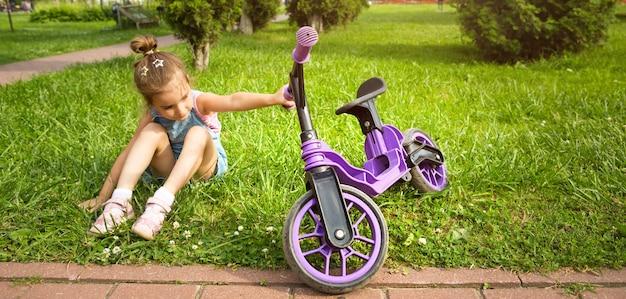 Menina alegre sentada descansando na grama em um parque perto de bicicleta roxa no verão