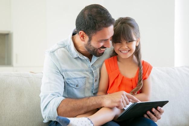 Menina alegre sentada no colo do pai, olhando para a câmera e rindo.