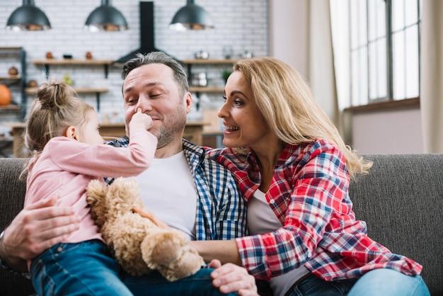 Menina alegre tocando o nariz do pai em casa