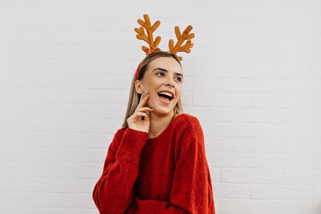 Menina alegre usa capacete de natal, sorrindo e se divertindo com um fundo isolado. foto de estúdio de camisola vermelha de mulher.